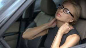 woman with neck pain sitting in a car