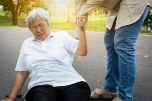 older person being helped up after a fall